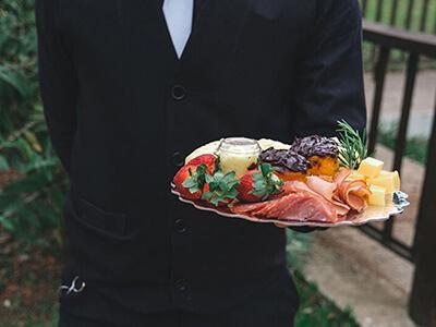 Garçom segurando bandeja com comidas e petiscos durante evento Life Garden da Celebrar Casa de Eventos