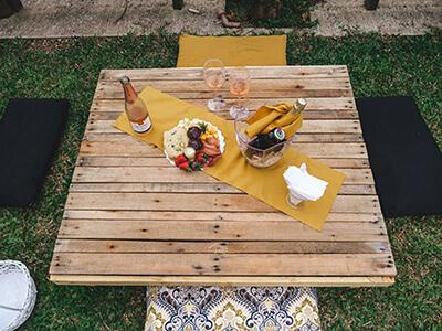 Mesa de pallet ao ar livre no jardim da Celebrar Eventos posta com bebidas e comidas para o evento Life Garden