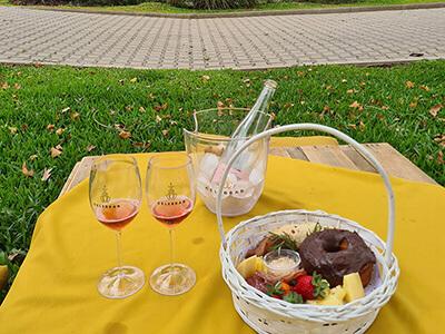 Cesta de comidas e pestiscos sobre mesa ao ar livre com cardápio sobre a mesa com logotipo da Celebrar Casa de Eventos